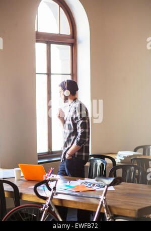 Pensive creative businessman with headphones looking out office window - Stock Photo