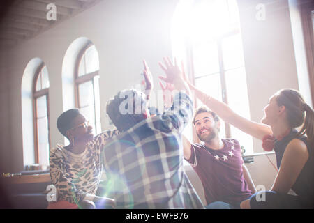 Casual business people raising hands in circle in sunny office meeting - Stock Photo