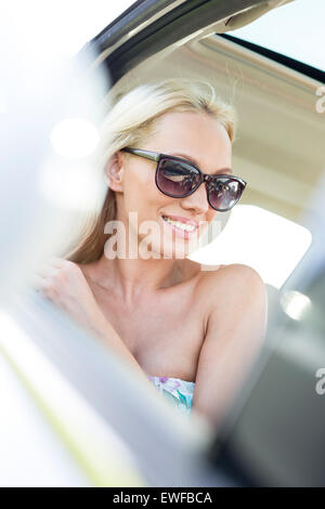 Happy woman looking away while sitting in car