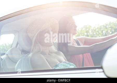 Young female friends in car on sunny day - Stock Photo