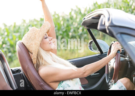 Side view of woman enjoying ride in convertible outdoors - Stock Photo