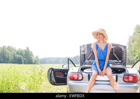 Young woman sitting on convertible trunk against clear sky - Stock Photo