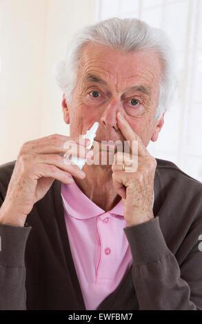 SENIOR USING NOSE SPRAY - Stock Photo
