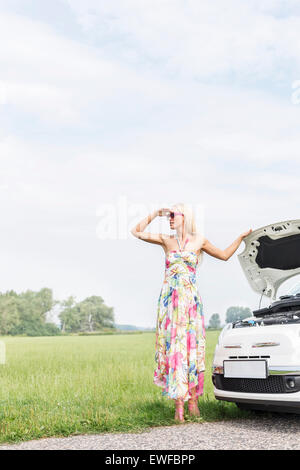 Woman shielding eyes while standing by broken down car on country road - Stock Photo