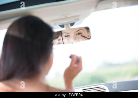 Reflection of woman using cell phone while applying mascara in rearview mirror of car - Stock Photo