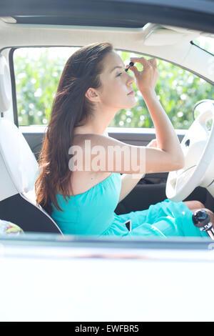 Young woman applying mascara in car - Stock Photo