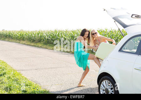 Happy female friends pushing luggage in car trunk against clear sky - Stock Photo