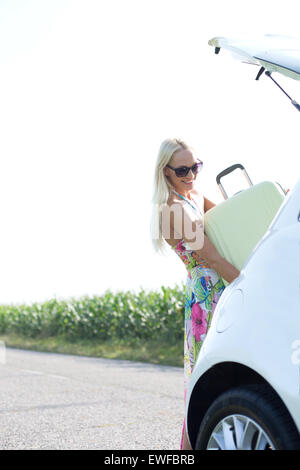 Happy woman loading suitcase in car trunk against clear sky - Stock Photo