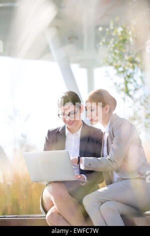 Happy businesswomen using laptop together on sunny day - Stock Photo