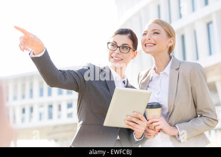Happy businesswoman showing something to colleague while using tablet PC - Stock Photo