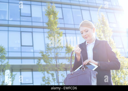 Businesswoman putting digital tablet in purse on sunny day - Stock Photo