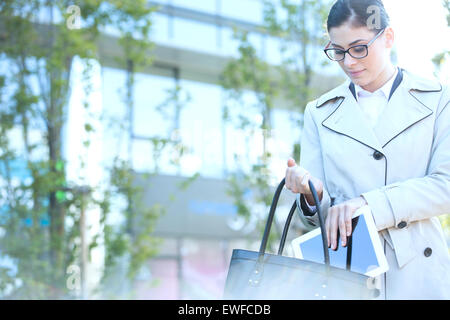 Businesswoman putting digital tablet in purse outdoors - Stock Photo