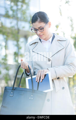 Businesswoman putting digital tablet in bag outdoors - Stock Photo