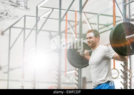 Smiling man lifting barbell at crossfit gym - Stock Photo