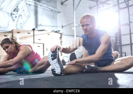 Confident man and woman doing stretching exercise in crossfit gym - Stock Photo