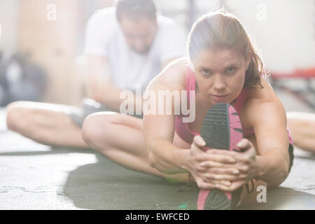 Portrait of confident woman doing stretching exercise in crossfit gym - Stock Photo