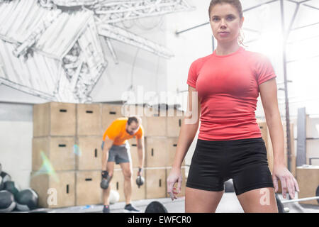 Portrait of confident woman standing in crossfit gym - Stock Photo