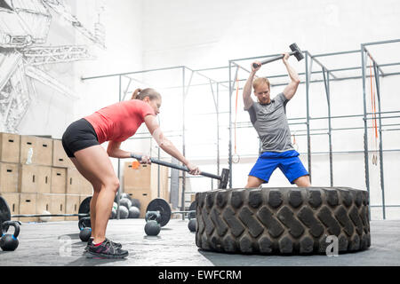 Man and woman hitting tire with sledgehammer in crossfit gym - Stock Photo