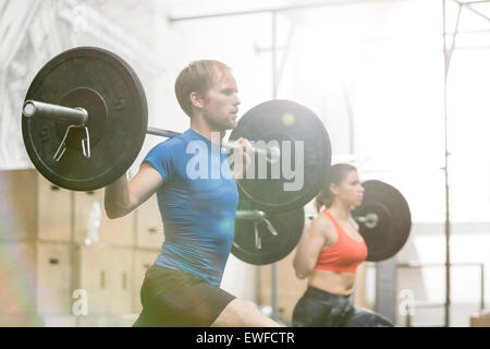 Man and woman lifting barbells in crossfit gym - Stock Photo