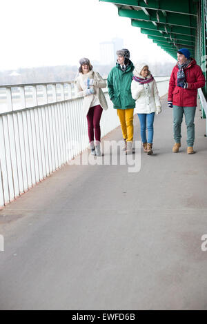 Multiethnic friends walking on footpath during winter - Stock Photo