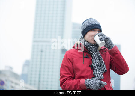 Man in warm clothing drinking coffee outdoors - Stock Photo