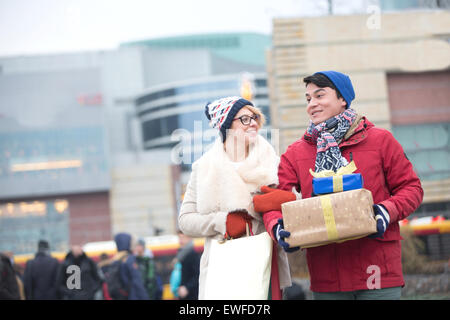 Happy couple with gifts and shopping bags walking in city during winter - Stock Photo