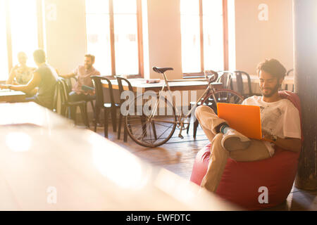 Casual businessman working at laptop in bean bag chair - Stock Photo