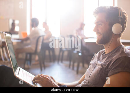 Casual businessman wearing headphones and working at laptop in office - Stock Photo