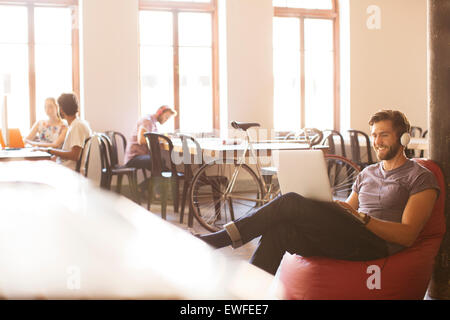 Smiling casual businessman wearing headphones and working at laptop on bean bag chair in office - Stock Photo