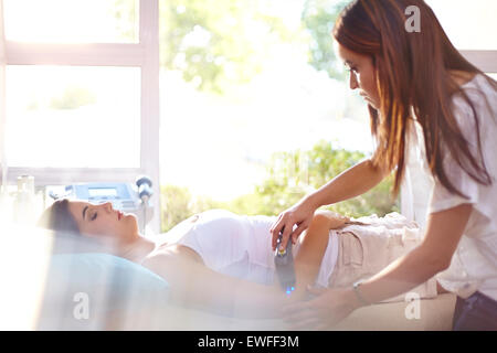 Physical therapist using ultrasound probe on woman's arm - Stock Photo