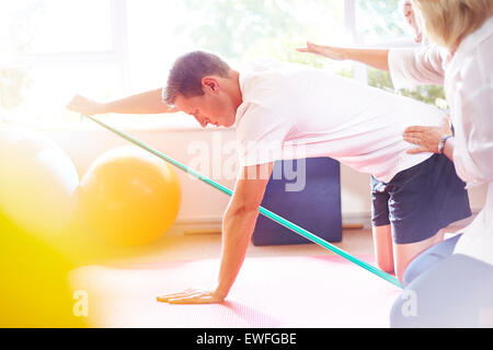 Physical therapist guiding man pulling resistance band - Stock Photo