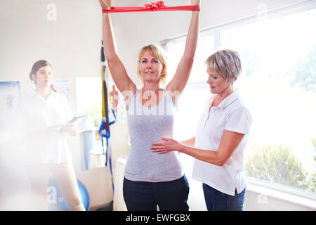 Physical therapist guiding woman pulling resistance band overhead - Stock Photo