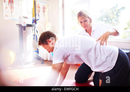 Physical therapist guiding man's back - Stock Photo