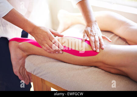 Physical therapist applying kinesiology tape to man's leg - Stock Photo