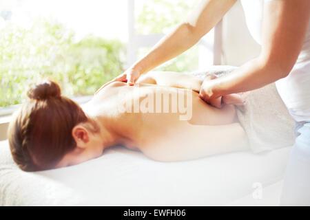 Masseuse massaging woman's back - Stock Photo