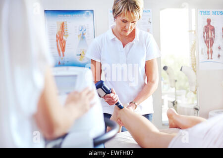Physical therapist using ultrasound probe on woman's leg - Stock Photo