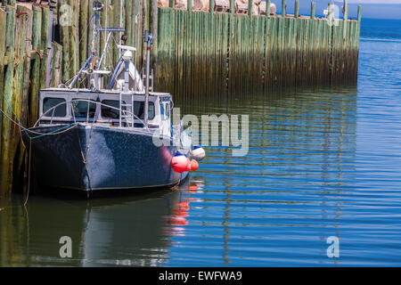 A lobster fishing boat tied up at the wharf in Hall's Harbour, Nova Scotia. - Stock Photo