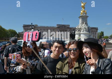 LONDON - MAY 13 2015:Chines tourists taking a selfie in Buckingham Palace. It's one of most popular tourist attractions - Stock Photo