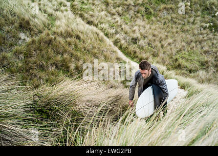 Surfer walking through sand dunes with his surfboard. - Stock Photo
