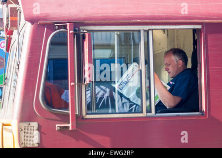 Freight train driver reading the Metro newspaper while train stopped at Southampton Central Station in June - Stock Photo