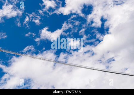 Image of a chain bridge in high altitude with blue sky and clouds - Stock Photo