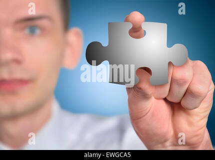 Man with puzzle piece in hand - Stock Photo