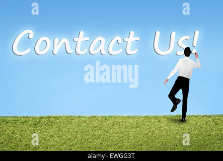 Business man writing on sky Contact us word - Stock Photo
