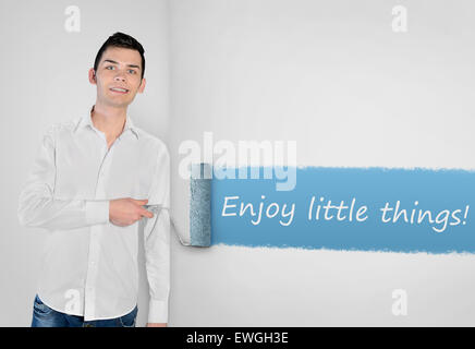 Young man painting Enjoy little things word on wall - Stock Photo