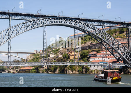Dom Luis I Bridge, which at upper level is both a walkway and a metro train line and cars on the lower level. Barges - Stock Photo