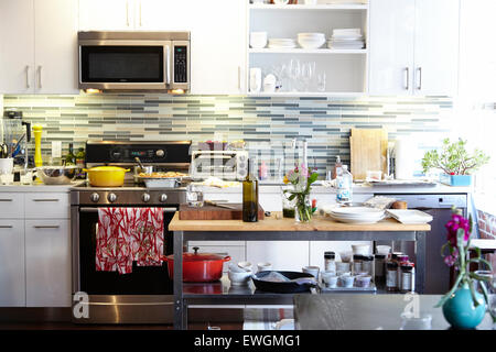 modern kitchen yellow pot red towel modern appliances white kitchen cabinets glass back splash wood island - Stock Photo