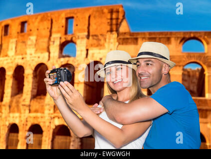 Beautiful couple taking picture of thyself on Coliseum background, happy young family spending summer vacation in - Stock Photo