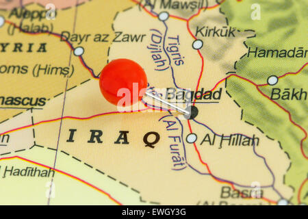 close up of a red pushpin on a map of baghdad iraq stock
