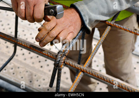 Worker using pincers and wire to tie steel reinforcing bars ...