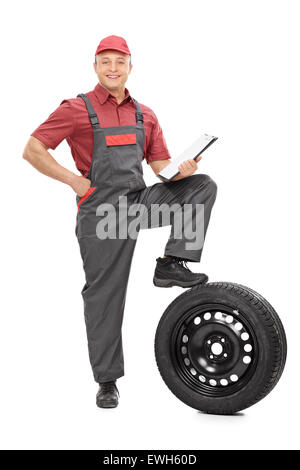 Full length portrait of a young mechanic holding a clipboard and looking at the camera isolated on white background - Stock Photo